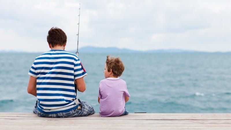 Far och son som sitter på brygga och fiskar